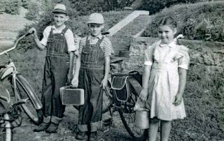 First day of school in 1949. I'm in the middle with my brother Cal and sister Marge on our way to ride our bikes to school. My little brother snuck in the picture too.